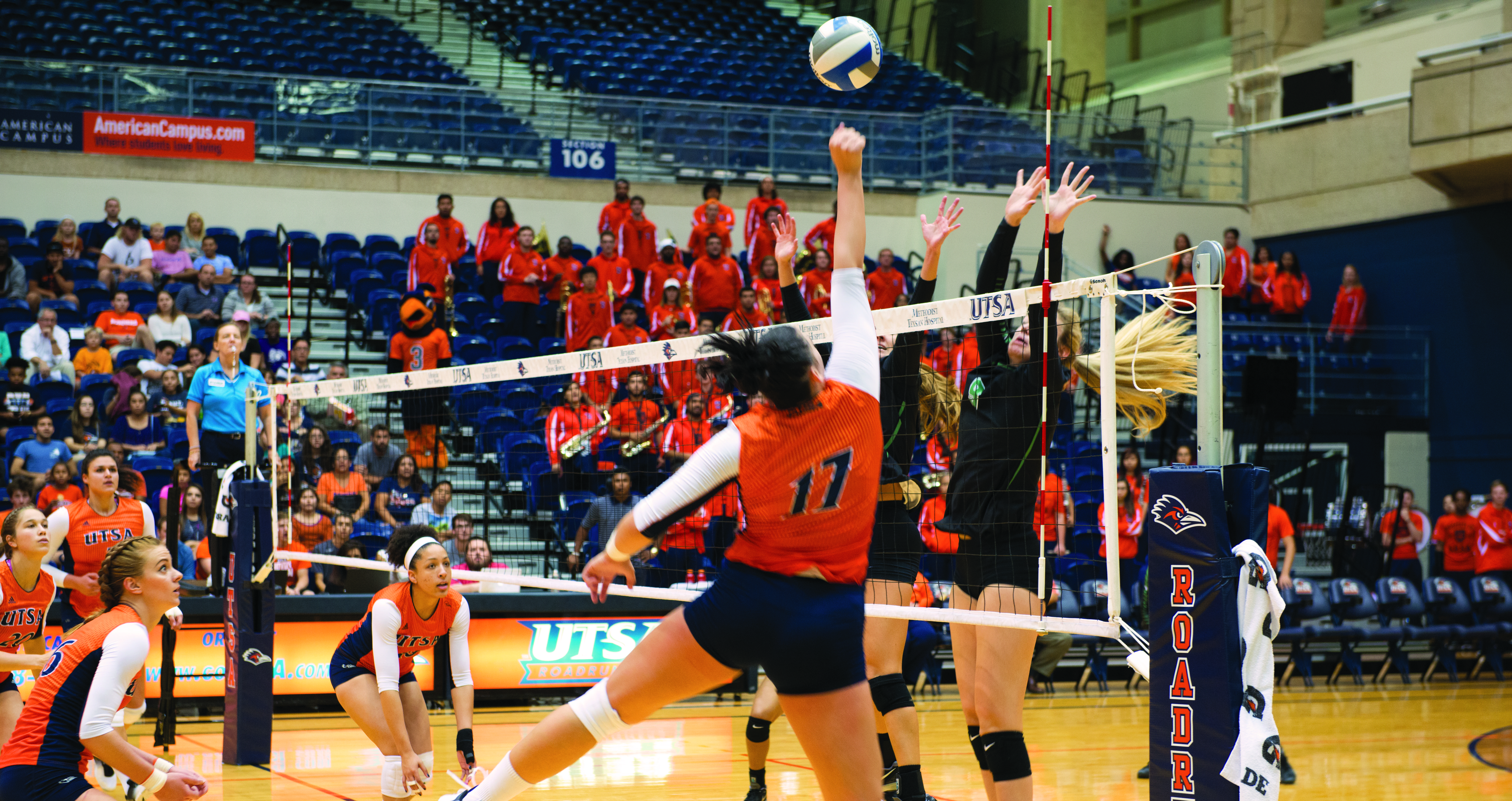 Volleyball player attempts to spike a ball.