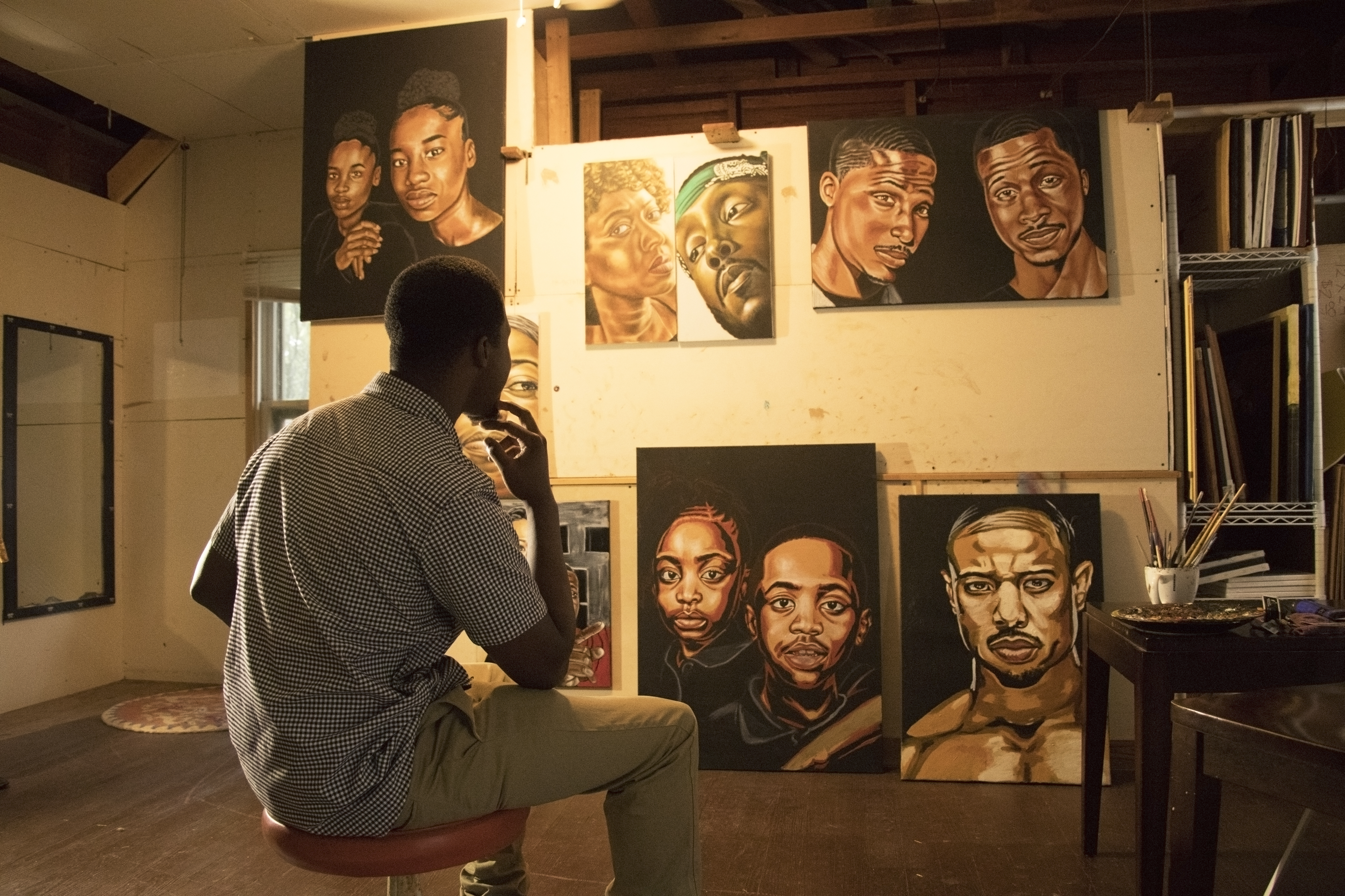 Kaldric Dow gazing at some of his works from East Side Portraits.