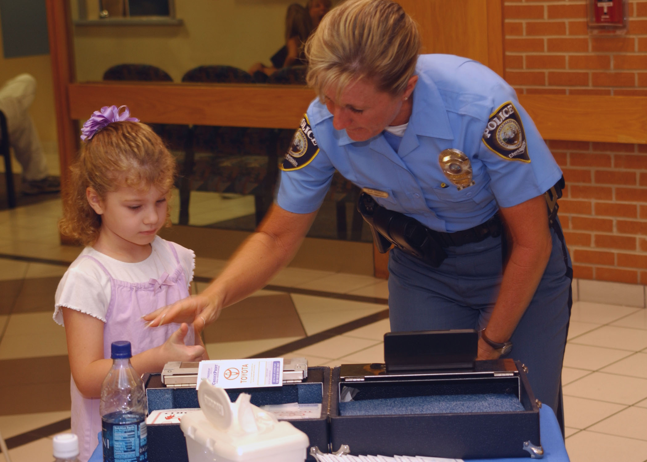 Officer Diane Branch with the Chesapeake Police Department takes children's fingerprints during the Ident-a-Kid program held at Naval Medical Center Portsmouth.
